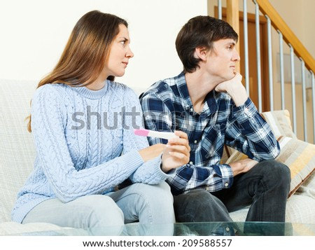 Sad worried woman with pregnancy test with unhappy man