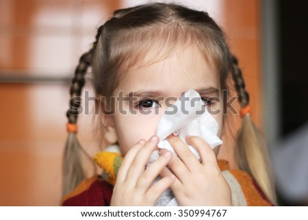 Sad young child (girl) with sick look and in the scarf on her throat blowing her nose in the napkin, indoor portrait