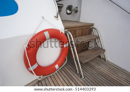 Safety equipment life buoy ring next to steps on teak deck of a luxury motor yacht