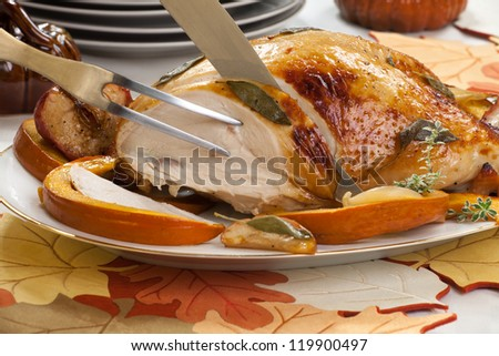 Sage - honey butter rub turkey breast garnished with roasted pumpkin and apples in fall themed surrounding.