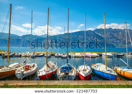 Sailing boats yachts on Garda lake. Veneto region. Italy. Landscape of marine regatta with floating in the harbor high Alpine mountains background