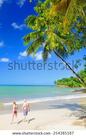 SAINT LUCIA, CARIBBEAN - DECEMBER 10, 2014: Senior couple walk by the beach in exotic resort in Saint Lucia, Caribbean