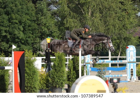 SAINT-PETERSBURG - JULY 07: Rider Marat Akhmetkhanov on Sakresine in Jumping show, stage of the International show jumping event CSI3*-W/CSIYH1*, on July 07, 2012 in Saint Petersburg, Russia.
