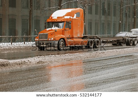 Saint-Petersburg, Russia, 25 Feb. 2016: Cargo truck on the urban highway in front of  wall with windows on a background. Truck on the road. Orange lorry on the asphalt city road in the evening time.