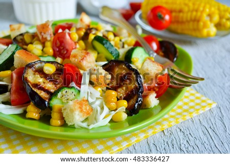 Salad with corn, tomatoes, eggplant and grilled croutons on a concrete background