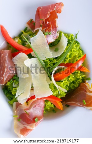Salad with parma and cheese on a white dish