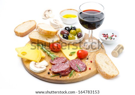 salami, cheese, bread, olives, tomatoes and glass of red wine isolated on white
