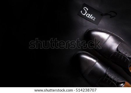 Sale sign. Black oxford shoes on black background. Top view. Copy space.