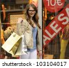 Sale: Young and happy woman shopping - stock