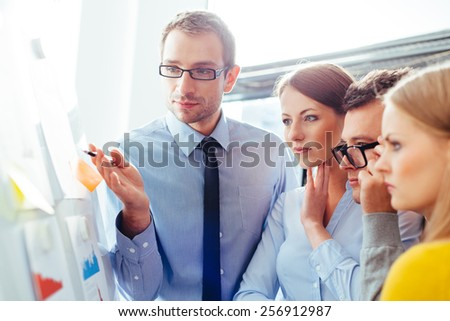 Sales representatives in a meeting with their manager and comparing their sales