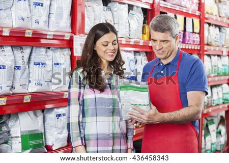 Salesman Assisting Customer In Buying Pet Food At Store