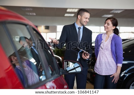 Salesman showing a car to a woman in a car shop