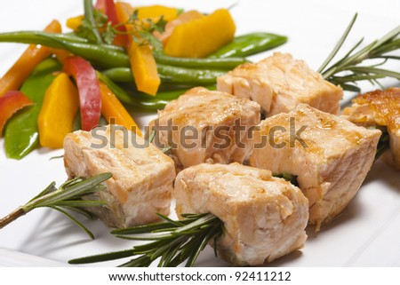 Salmon grilled on the rosemary skewers with vegetables