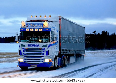 SALO, FINLAND - JANUARY 7, 2017: Customized Super Scania of T. Salminen Transport semi trailer moves along snowy highway at dusktime in South of Finland.