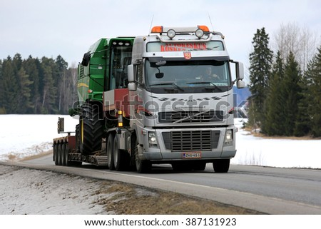 SALO, FINLAND - MARCH 4, 2016: Volvo FH16 truck hauls John Deere W330 combine harvester on lowboy trailer along highway. The W330 is a compact combine designed for farming on a smaller scale.