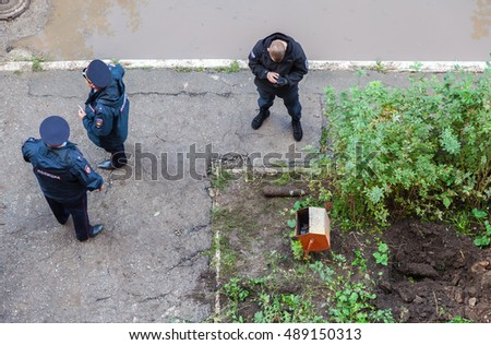 SAMARA, RUSSIA - SEPTEMBER 22, 2016: Russian police stand near old rusty artillery shell, found in digging trenches