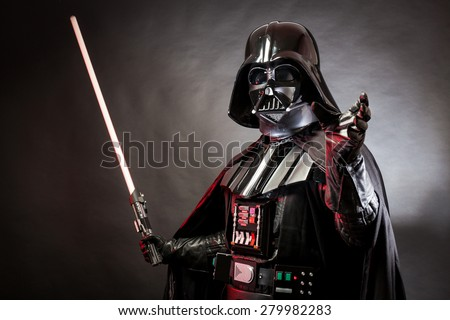 SAN BENEDETTO DEL TRONTO, ITALY. MAY 16, 2015. Portrait of Darth Vader costume replica with grab hand and his sword . Darth Vader is a fictional character of Star Wars saga.  Red grazing light