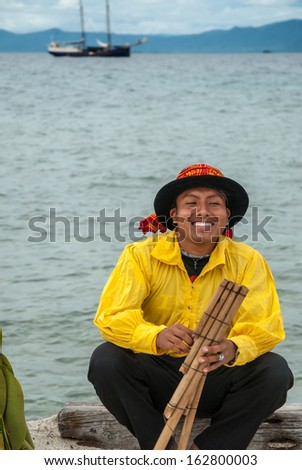 SAN BLAS ISLANDS, PANAMA - CIRCA JUNE 2006. Unknown native Kuna Indian man dressed  in native cerimonial attire playing a hand made flute in the San Blas Islands, panama, CIRCA June 2006.