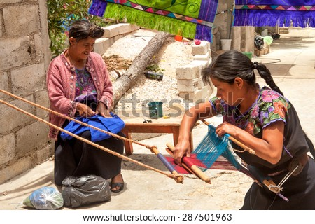 San Lorenzo Zinacantan, Mexico - May 10, 2014: Indigenous Tzotzil women weaving a traditional Huipil at the loom.