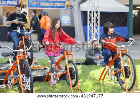 SAN MATEO, CA May 20 2016 - Members of the audience pedal stationary bicycles to power a musical performance during the 11th annual Bay Area Maker Faire at the San Mateo County Event Center.