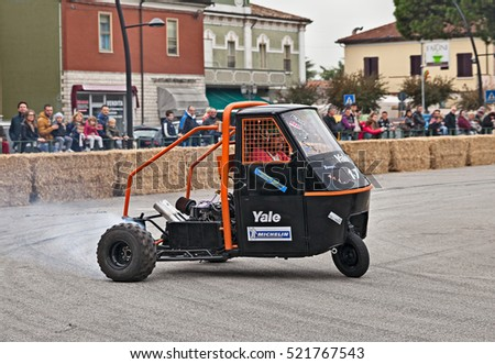 "SAN PIETRO IN VINCOLI, RA, ITALY - OCTOBER 23: driver on a three-wheeled vehicle Ape Piaggio with Kawasaki GPZ engine in ""Telethon Motor Show"" on October 23, 2016 in San Pietro in Vincoli, RA, Italy"