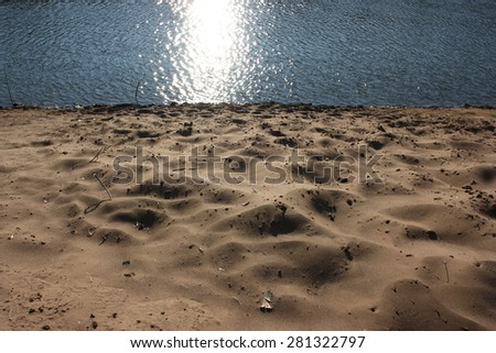 Sand beach and sparkling river water