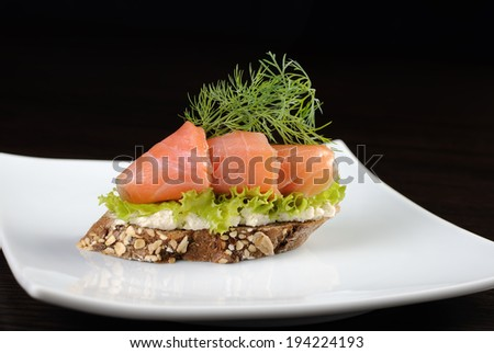 Sandwich of rye bread with salmon and ricotta
