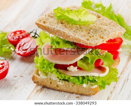 Sandwich with turkey and fresh vegetables on a  wooden table  - healthy eating