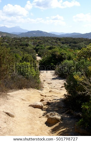 Sandy coastal hiking track with boulders through maquis vegetation, view to the mountains at the horizon; Coast near Tizzano, Corsica, France (2014)