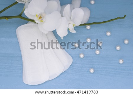 Sanitary pads and lilac orchid on the blue wooden background. Woman hygiene protection