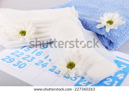 Sanitary pads, calendar, towel and white flowers on light background