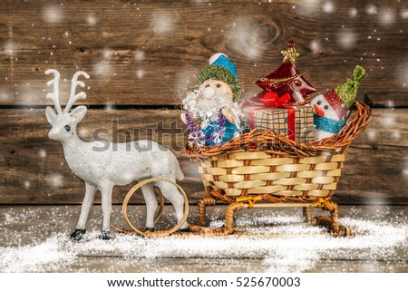 Santa and snowman in a reindeer sleigh with gifts.