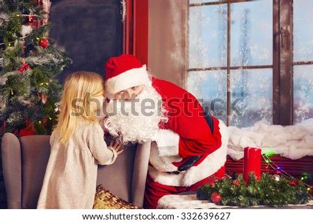 Santa Claus and little girl. Christmas Scene. Girl telling her Christmas wish in Santa Claus near the Christmas Tree