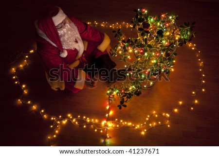 Santa Claus decorating a plant like a christmas tree