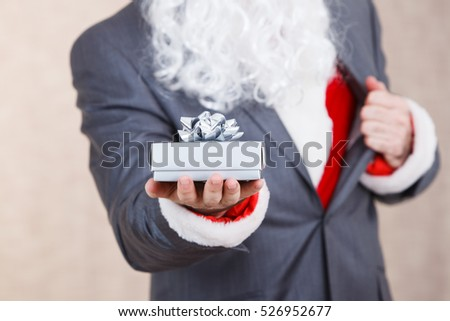Santa Claus holding a gift box with ribbon