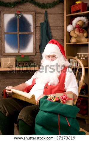 Santa Claus in Rocking Chair with Naughty List and Bag of Toys, vertical composition