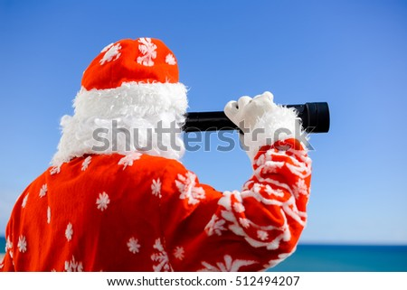 Santa Claus looking through telescope on sunny blue sky copyspace outdoors background. Closeup back side view image
