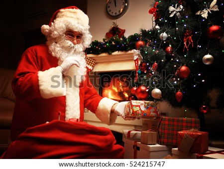 Santa Claus putting gift box or present under Christmas tree at eve night. It's a secret. Surprise. Don't tell the kids. Xmas and New Year holiday.