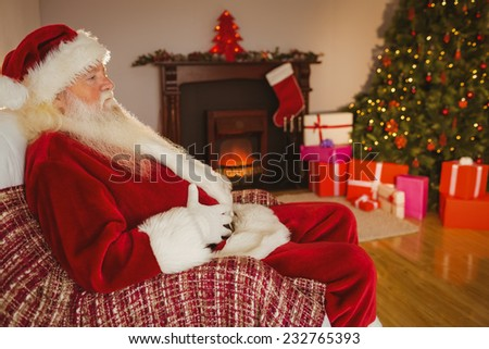 Santa claus sitting and holding his belly at home in the living room