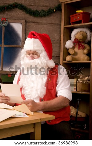 Santa Claus Sitting in His Workshop reading a letter. Vertical Composition.