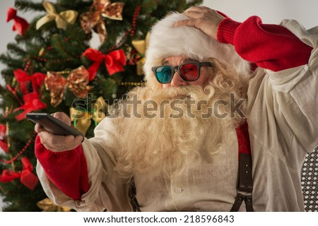 Santa Claus sitting in rocking chair near Christmas Tree at home and watching tv or home theater wearing 3d glasses and holding remote control