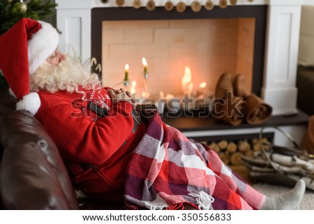 Santa Claus Warming near Fireplace at Home