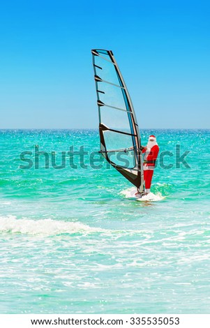 Santa Claus windsurfer go surfing with sailboard at ocean waves in tropical sunny windy weather - New Year's and Christmas vacation concept