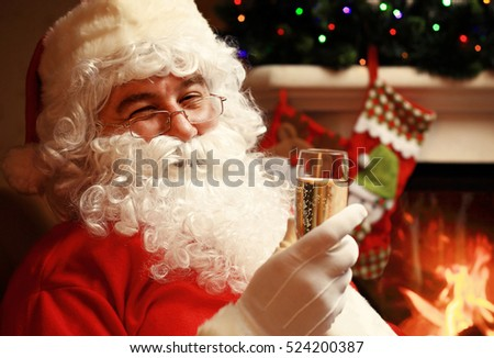 Santa Claus with a glass of sparkling wine champagne near a Christmas tree