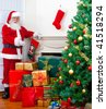 Santa with gifts next to a Christmas tree - stock photo
