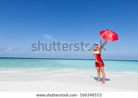 Santa woman standing at the beautiful white sand beach and holding the Christmas red umbrella. Copy space