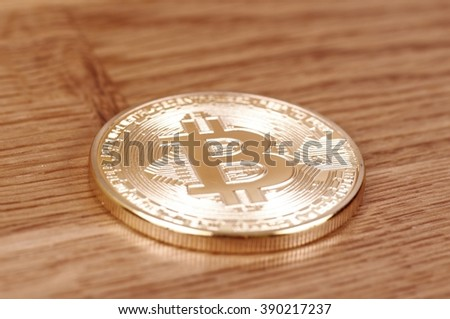 Saransk, Russia - March 12, 2016: Gold-plated bitcoin on a wooden background.