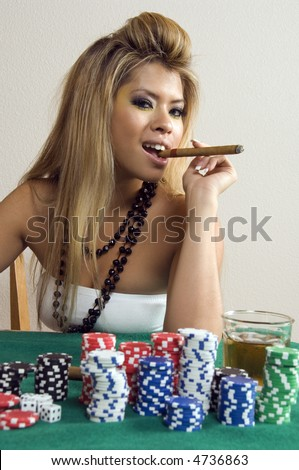 Sassy young Asian-American woman holds cigar between her teeth near stacks of poker chips and drink