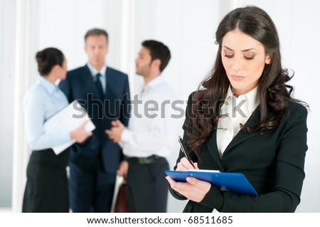 Satisfied smiling business woman compiling a form for a job recruitment or interview at office