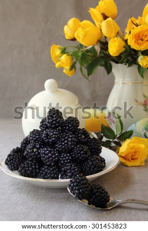 Saucer with blackberries and a vase with yellow roses.